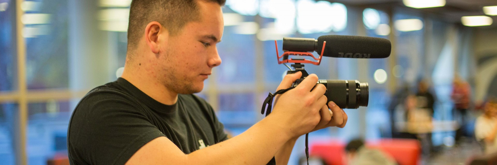 Male student employee using a video camera