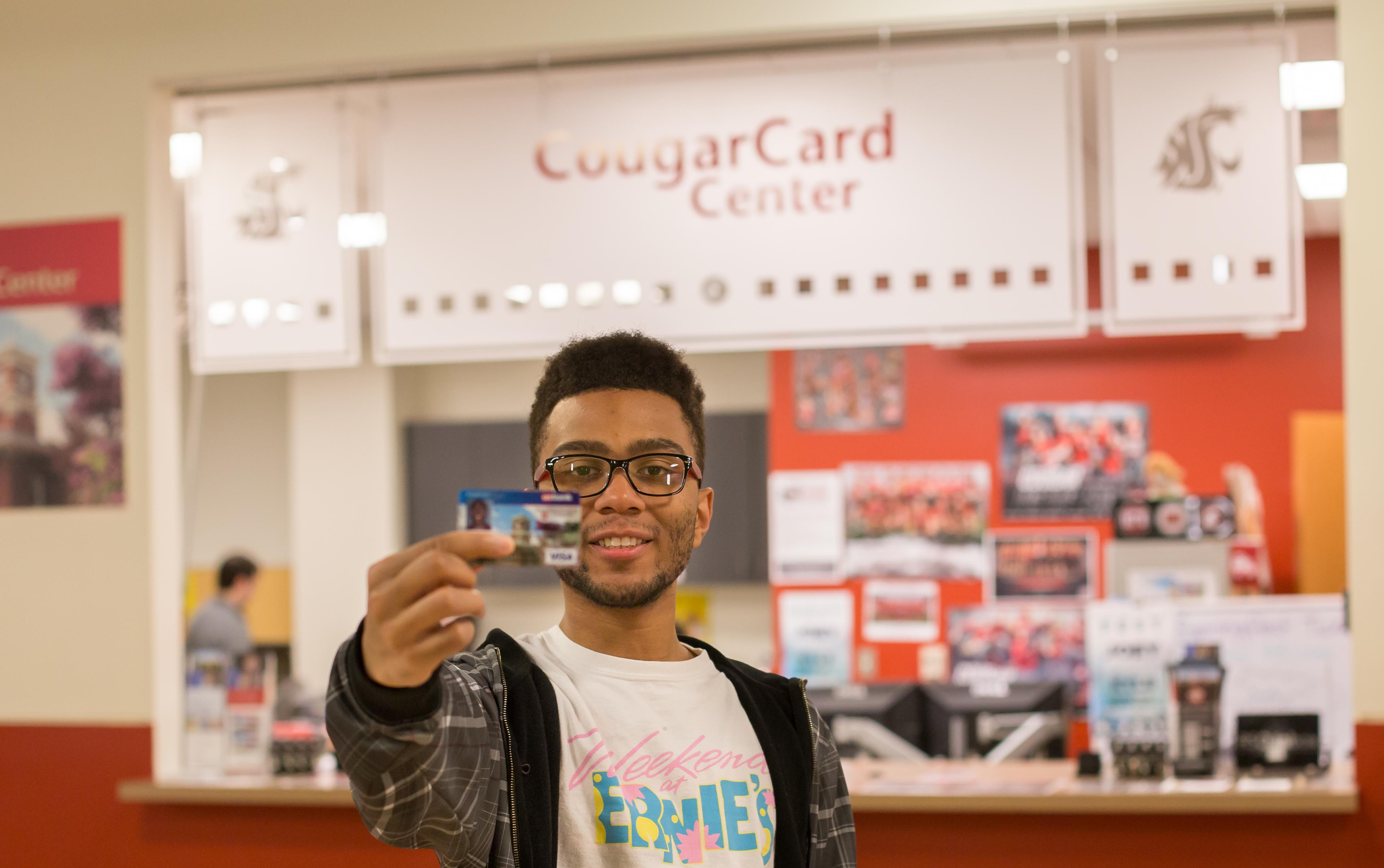 Student holding a CougarCard facing the camera